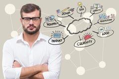 Ψηφιακή σύνθετη εικόνα του επιχειρηματία με τα όπλα που διασχίζονται από τα εικονίδια που περιβάλλουν το σύννεφο Στοκ Φωτογραφίες