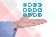 Ψηφιακή σύνθετη εικόνα του χεριού με τα ιατρικά εικονίδια Στοκ εικόνα με δικαίωμα ελεύθερης χρήσης