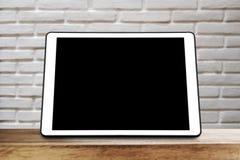Ψηφιακή ταμπλέτα στον ξύλινο πίνακα με το άσπρο υπόβαθρο τούβλων στοκ φωτογραφία
