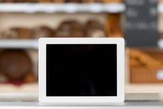 Ψηφιακή ταμπλέτα στο μετρητή καταστημάτων αρτοποιείων στοκ εικόνα με δικαίωμα ελεύθερης χρήσης