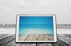 Ψηφιακή ταμπλέτα στο ξύλινο γραφείο στην τροπική παραλία Στοκ εικόνα με δικαίωμα ελεύθερης χρήσης
