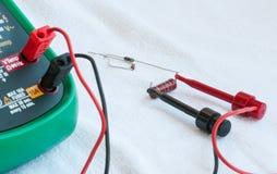 Ψηφιακό πολύμετρο που μετρά έναν αντιστάτη Στοκ φωτογραφία με δικαίωμα ελεύθερης χρήσης