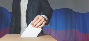 Ψηφοφόρος ατόμων που βάζει την ψήφο στην ψηφοφορία του κιβωτίου Έννοια ελευθερίας δημοκρατίας στο υπόβαθρο σημαιών Στοκ Φωτογραφία
