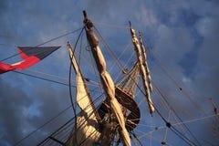 Ψηλοί ιστοί και ξάρτια σκαφών που σκιαγραφούνται ενάντια σε έναν δραματικό ουρανό στο ηλιοβασίλεμα Στοκ Εικόνες