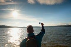 Ψηλός τουρίστας ατόμων τρίχας πιπεροριζών που παίρνει τις φωτογραφίες ή το βίντεο με το κινητό τηλέφωνο Ηλιόλουστη ημέρα φθινοπώρ στοκ εικόνα με δικαίωμα ελεύθερης χρήσης