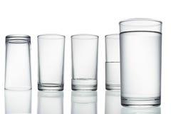 Ψηλό κενό, μισό και πλήρες ποτήρι του νερού στο λευκό με Στοκ Εικόνες