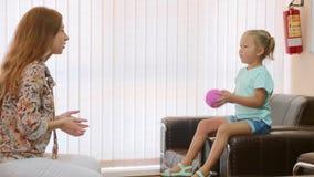 Ψυχολόγος που εξετάζει λίγο κορίτσι παιδιών κατά τη διάρκεια των παιχνιδιών σφαιρών απόθεμα βίντεο