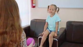 Ψυχολόγος που εξετάζει λίγο κορίτσι παιδιών κατά τη διάρκεια των παιχνιδιών σφαιρών φιλμ μικρού μήκους