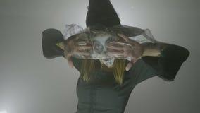 Ψυχο μάγισσα με το καπέλο και πέπλο που κινείται με έναν τρομακτικό τρόπο και που δοκιμάζει τις κακές εκφράσεις προσώπου για αποκ απόθεμα βίντεο