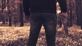 Ψυχο μανιακό άτομο με ένα μεγάλο κυνηγετικό μαχαίρι σε ένα πάρκο απόθεμα βίντεο