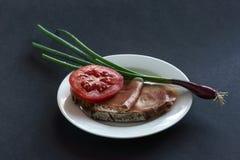 Ψωμί ζαμπόν με την ντομάτα και πράσο στο πιάτο, γκρίζο υπόβαθρο στοκ φωτογραφίες