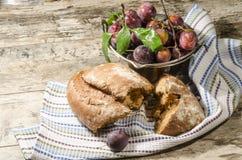 Ψωμί και δαμάσκηνο στον παλαιό ξύλινο πίνακα Στοκ Φωτογραφία
