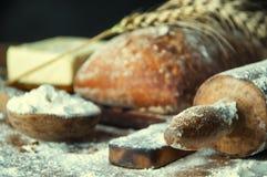 Ψωμί και προσθήκες σε έναν ξύλινο πίνακα Στοκ Φωτογραφίες