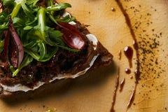 Ψωμί με τα μαγειρευμένα ψημένα κρέας κρεμμύδια και arugula στο πιάτο Στοκ φωτογραφία με δικαίωμα ελεύθερης χρήσης