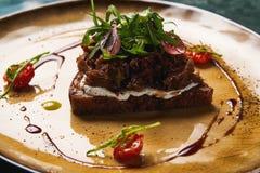 Ψωμί με τα μαγειρευμένα ψημένα κρέας κρεμμύδια και arugula στο πιάτο Στοκ Φωτογραφία