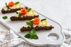 Ψωμί με τη φρέσκια λωρίδα σολομών, το τυρί κρέμας και το λεμόνι στο άσπρο πιάτο, πλάγια όψη Το διάστημα αντιγράφων, κλείνει επάνω στοκ φωτογραφίες