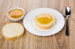 Ψωμί με το μέλι στο πιάτο, κουταλάκι του γλυκού, κύπελλο με το μέλι Στοκ φωτογραφία με δικαίωμα ελεύθερης χρήσης