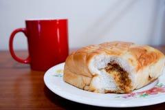 Ψωμί νήματος χοιρινού κρέατος και μια κόκκινη κούπα καφέ στοκ εικόνες