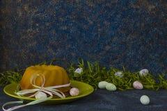Ψωμί Πάσχας στο πράσινο πιάτο και το χρωματισμένο πίνακα πετρών αυγών Πάσχας ιονικό σκοτεινό που διακοσμούνται με την πράσινη χλό στοκ φωτογραφία με δικαίωμα ελεύθερης χρήσης