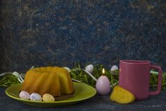 Ψωμί Πάσχας στο πράσινο πιάτο, τη ρόδινη κούπα και τα χρωματισμένα αυγά Πάσχας στοκ φωτογραφία