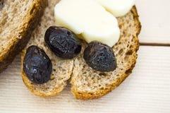 Ψωμί πίτουρου και εκτός από τις μαύρες ελιές, το τυρί, το ομορφότερο τυρί προγευμάτων και τις μαύρες ελιές Στο διαφορετικό ψωμί ε Στοκ εικόνες με δικαίωμα ελεύθερης χρήσης