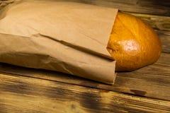 Ψωμί που συσκευάζεται στο έγγραφο για τον ξύλινο πίνακα Στοκ Φωτογραφία