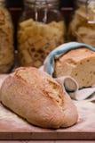 Ψωμί που τοποθετούνται σε έναν τεμαχίζοντας πίνακα, με τα κύπελλα ζυμαρικών στο backgrou Στοκ Φωτογραφίες