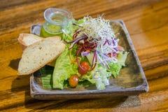 Ψωμί, πράσινη vagatable και σαλάτα ντοματών στο plade στον ξύλινο πίνακα στοκ εικόνες με δικαίωμα ελεύθερης χρήσης