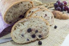 Ψωμί φρούτων με το aronia που τεμαχίζεται σε ένα ξύλινο πιάτο με το ξηρό aron Στοκ Φωτογραφία