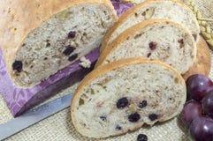 Ψωμί φρούτων με το aronia που τεμαχίζεται σε ένα ξύλινο πιάτο με το ξηρό aron Στοκ Εικόνες