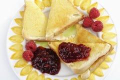 Ψωμί φρυγανιάς με τη μαρμελάδα βουτύρου και σμέουρων στο πιάτο Στοκ Φωτογραφία