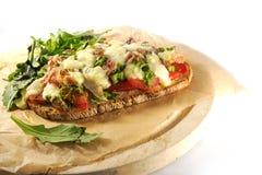 Ψωμί Gratinated με τα κρεμμύδια, το μπέϊκον και τη μοτσαρέλα άνοιξη ντοματών Στοκ Εικόνες
