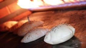 Ψωμί Pita στο φούρνο Το Pita ή pide πασπαλίζει με ψίχουλα καλυμμένος με το αυγό και το σουσάμι επάνω στο ξύλινο κουπί στο φούρνο  απόθεμα βίντεο