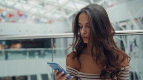 Ψωνίζοντας γυναίκα που χαμογελά με τις τσάντες που μιλούν στο τηλέφωνο στη λεωφόρο Όμορφο κορίτσι με το smartphone στις αποσκευές απόθεμα βίντεο