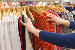 ψωνίζοντας λευκή γυναίκα ποδιών έννοιας τσαντών ανασκόπησης Η γυναίκα επιλέγει τα πουκάμισα στις κρεμάστρες σε ένα κατάστημα ιματ Στοκ εικόνα με δικαίωμα ελεύθερης χρήσης