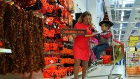 Ψωνίζοντας σε μια μεγάλη υπεραγορά σε αποκριές, τη μητέρα και το γιο που προετοιμάζονται για την παραμονή όλου του Hallows, εορτα απόθεμα βίντεο