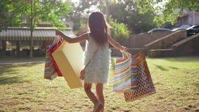 Ψωνίζοντας, το εύθυμο παιδί είναι ευχαριστημένο από τις νέες αγορές σε πολλές συσκευασίες στα αυξημένα χέρια που πηδούν στον πράσ φιλμ μικρού μήκους