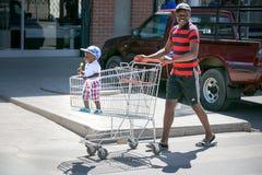 Ωθώντας αγοράκι πατέρων στο καροτσάκι αγορών στοκ εικόνα
