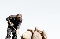 Ωθώντας πέτρες ατόμων με το pitchfork σε ένα φωτεινό υπόβαθρο ουρανού στοκ φωτογραφίες