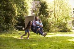 Ωθώντας πατέρας και γιος κορών στην ταλάντευση ροδών στον κήπο στοκ εικόνες