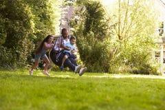 Ωθώντας πατέρας και γιος κορών στην ταλάντευση ροδών στον κήπο στοκ εικόνα