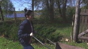 Ωθώντας wheelbarrow γυναικών στον κήπο φιλμ μικρού μήκους