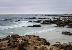 Ωκεάνια ακτή με τα κύματα και τους βράχους Μπλε μαύροι βράχοι νερού στοκ φωτογραφία