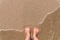 Ωκεάνια κύματα θάλασσας και πόδια κοριτσιών στην αμμώδη παραλία Στοκ φωτογραφίες με δικαίωμα ελεύθερης χρήσης