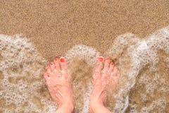 Ωκεάνια κύματα θάλασσας και πόδια κοριτσιών στην αμμώδη παραλία Στοκ Φωτογραφίες