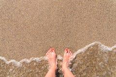 Ωκεάνια κύματα θάλασσας και πόδια κοριτσιών στην αμμώδη παραλία Στοκ εικόνα με δικαίωμα ελεύθερης χρήσης
