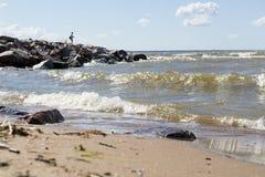 Ωκεάνια κύματα που περιτυλίγουν στην αμμώδη ακτή, μακριά κορίτσι που στέκεται στο θόριο Στοκ Εικόνες