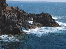 Ωκεάνια κύματα που σπάζουν στη δύσκολη ακτή της λάβας με τα σπήλαια και τις κοιλότητες Βουνά και ηφαίστεια στον ορίζοντα στοκ εικόνες