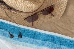 ωκεάνιο κοχύλι θάλασσας έννοιας παραλιών ανασκόπησης Θηλυκά καπέλο, γυαλιά ηλίου, πετσέτα και ακουστικά, στην άμμο Στοκ Φωτογραφία