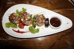 Ωραία διακοσμημένο πιάτο κρέατος σε ένα πιάτο τριγώνων Στοκ Φωτογραφία